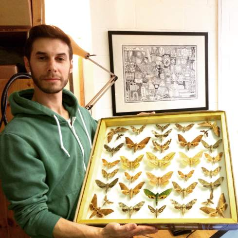 Alex and his collection of moths. In the back, prints of their dad's artwork